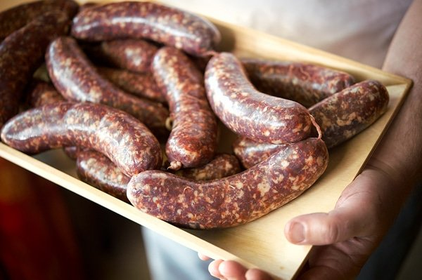 Holding a tray of loukaniko sausage