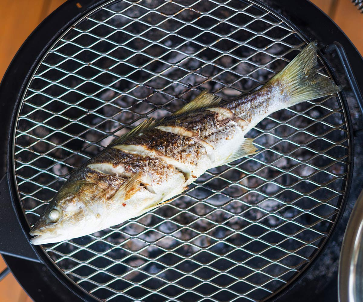 A grilled whole fish over the coals.