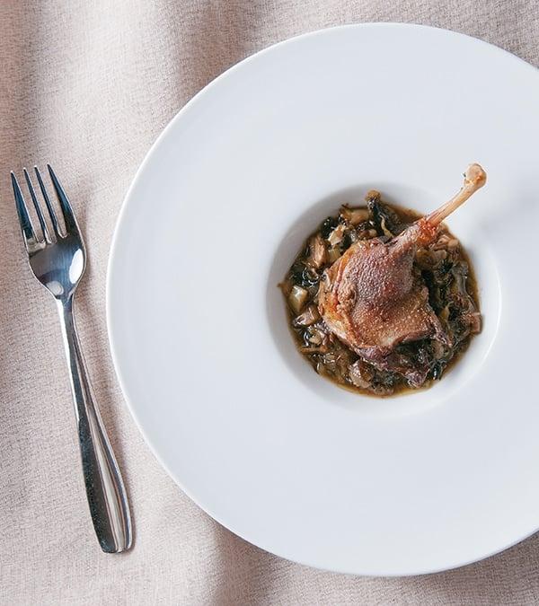Braised duck legs with leeks, on a fancy plate