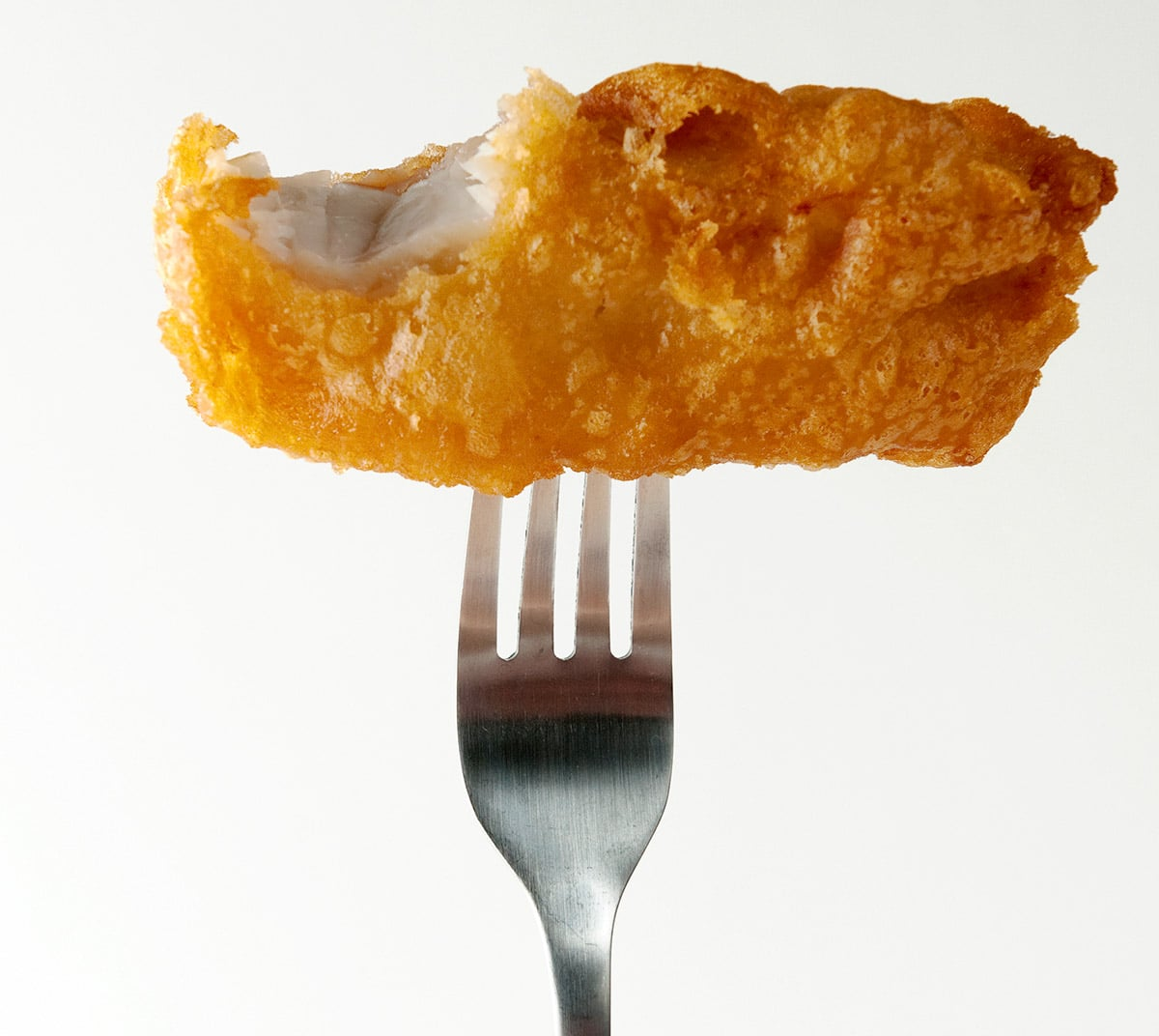 Beer battered fish and chips on a fork