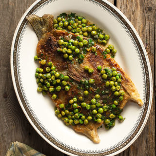 Pan fried trout with peas on a platter
