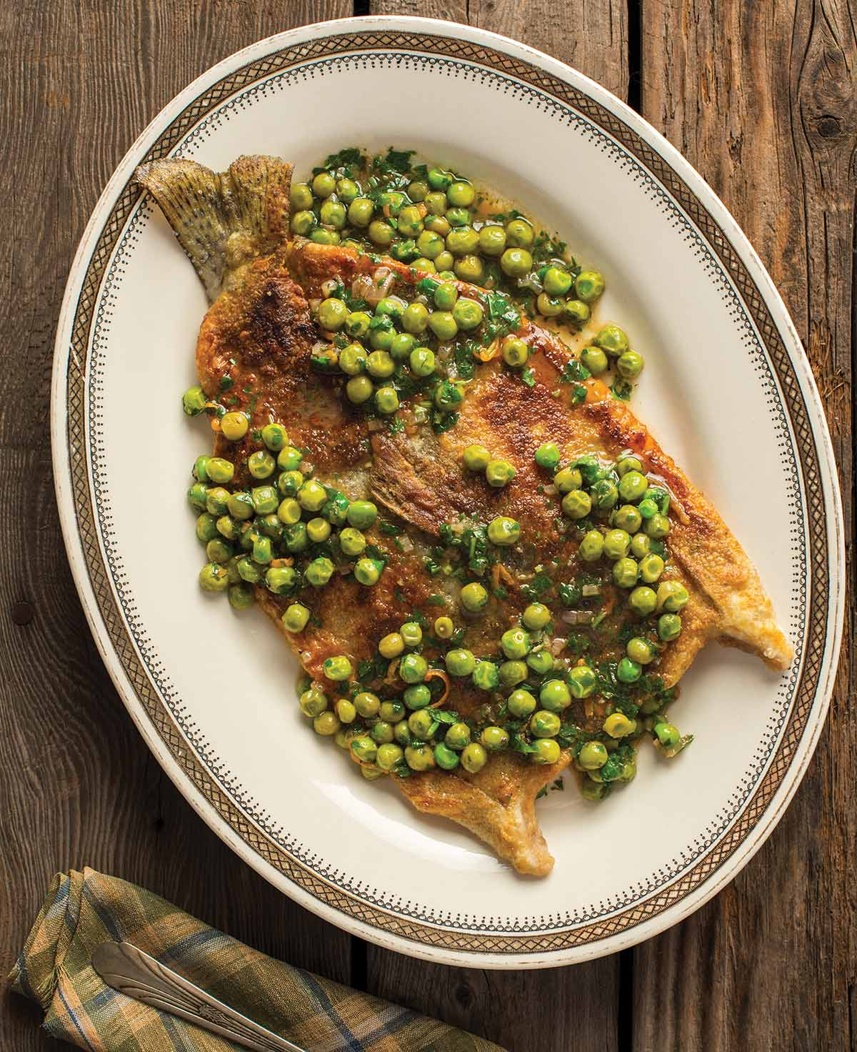 A plate of pan fried trout with peas