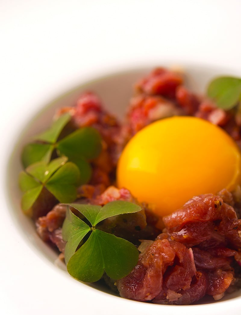 A bowl of venison tartare with an egg yolk.