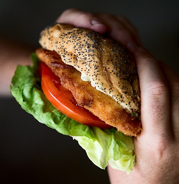 Holding a fried fish sandwich