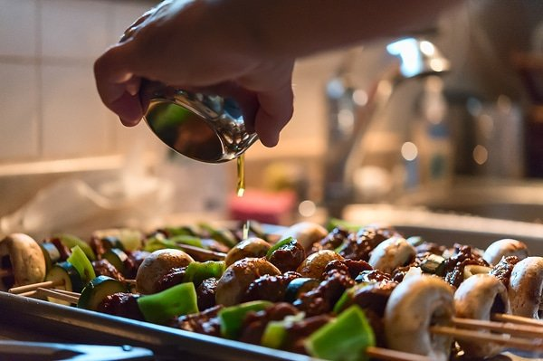 Pouring olive oil on venison kebabs before grilling