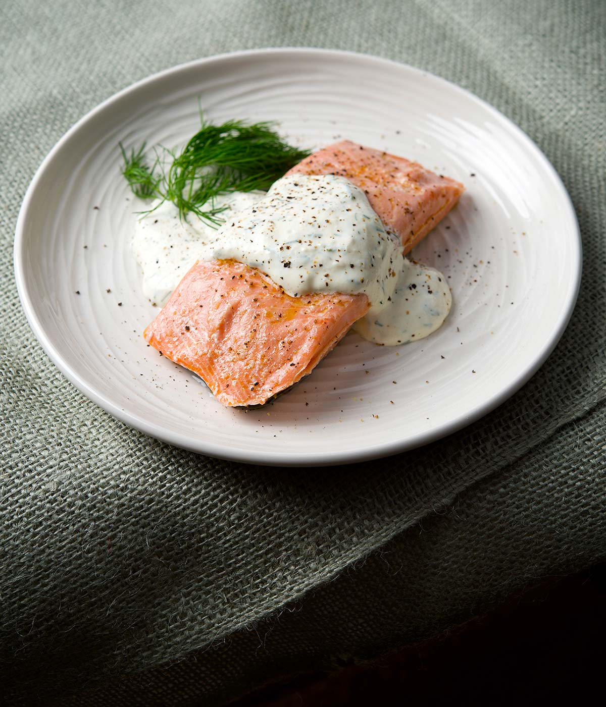 Butter poached salmon with dill sauce on a plate