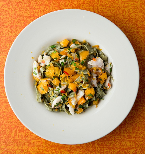 A bowl of kelp pasta with fish and summer vegetables.