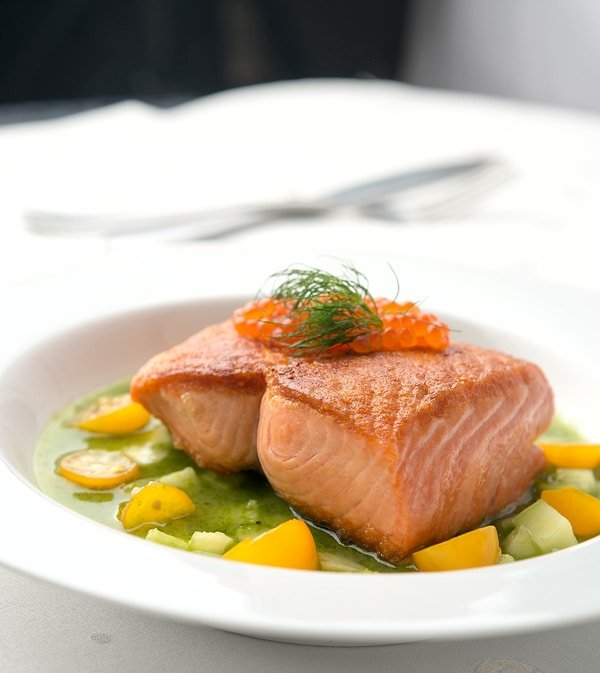 salmon with cucumber sauce on the plate