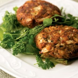 Midwestern fish cakes on a plate with a green salad.