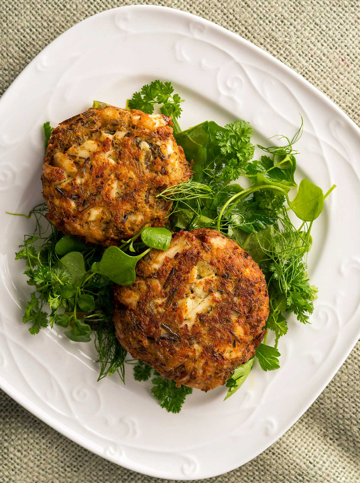 Finished fish cakes recipe on a plate with a green salad.
