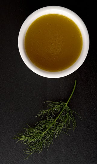 finished fish stock with a fennel frond