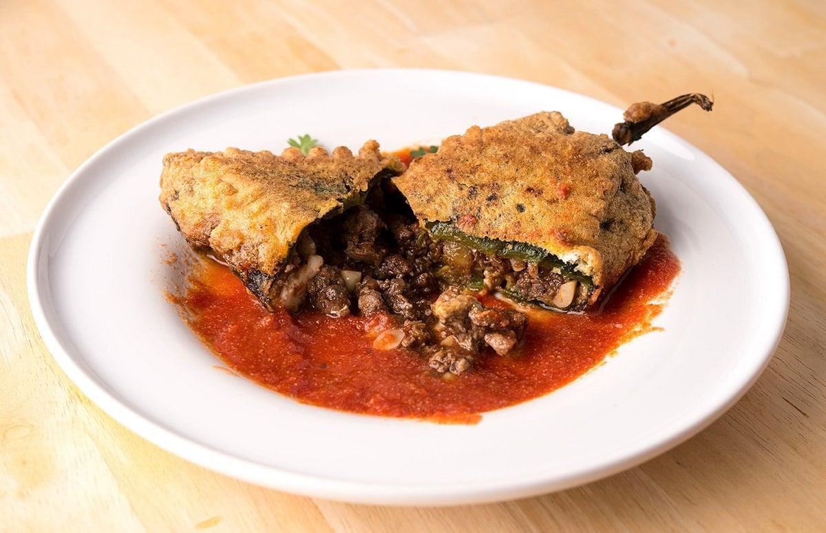 A broken open chile poblano rellenos on a plate
