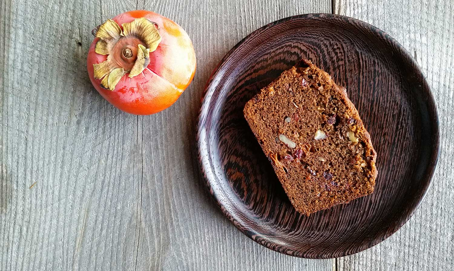 overhead view of persimmon bread, with a hachiya persimmon