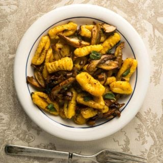 A bowl of butternut squash gnocchi with mushrooms