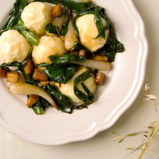 Ricotta gnudi on a plate with onions and mushrooms