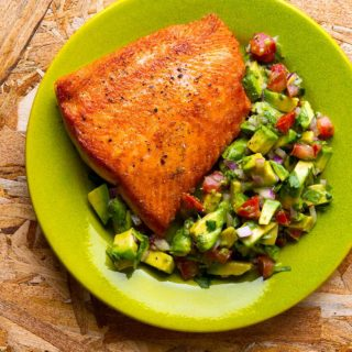 Seared salmon with avocado salsa on a plate