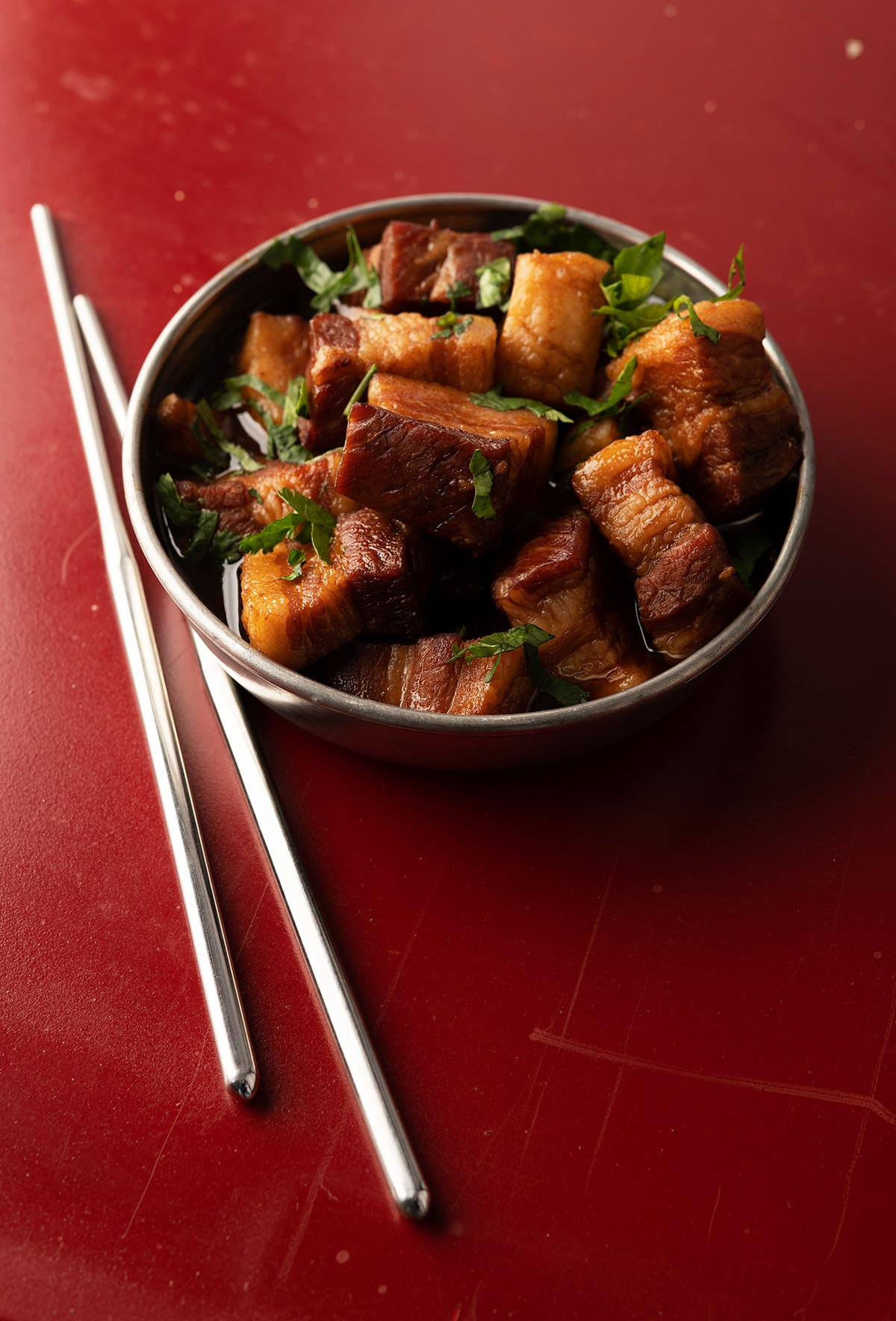 Chinese red pork in a bowl with chopsticks