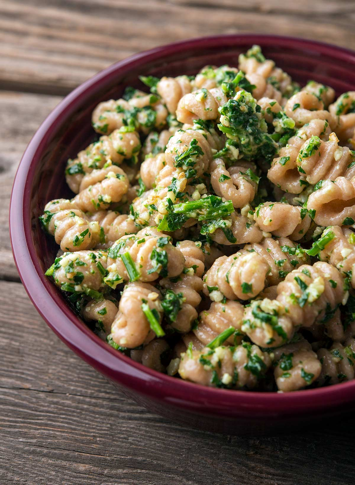 Parsley pesto mixed with pasta in a bowl