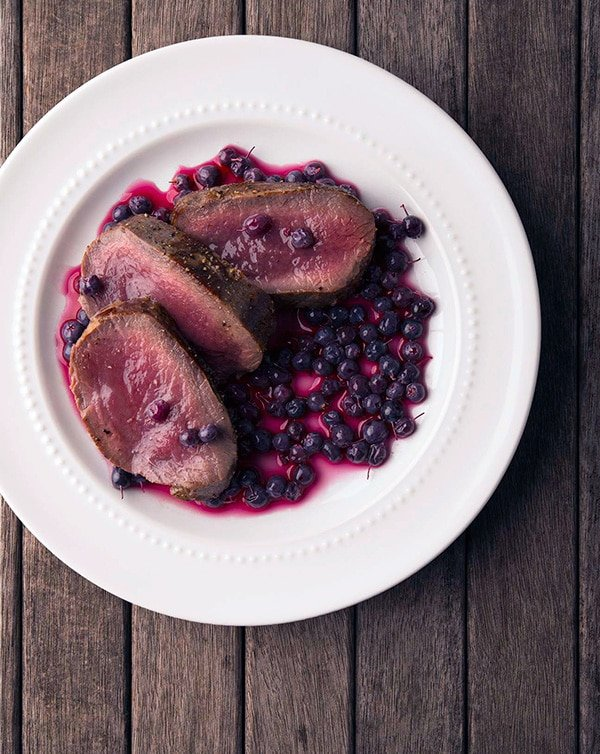 pickled blueberries with venison steak on a plate