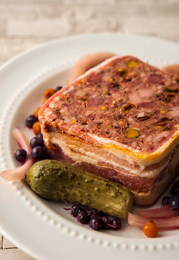 A slice of wild game terrine with pickles