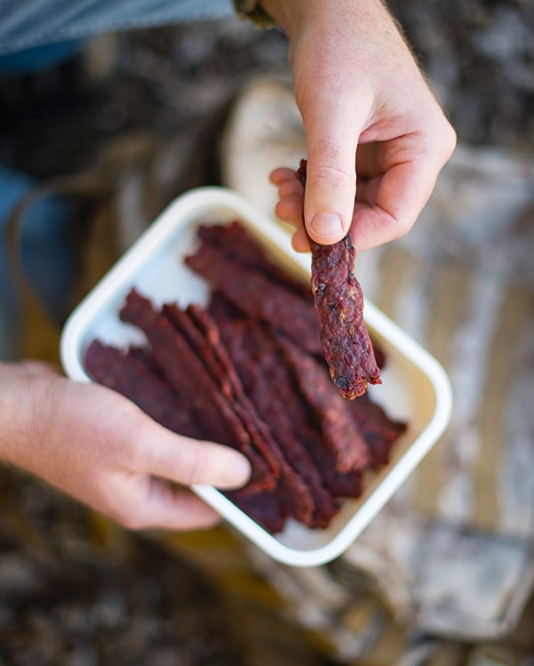 Hank Shaw holding a piece of ground venison jerky