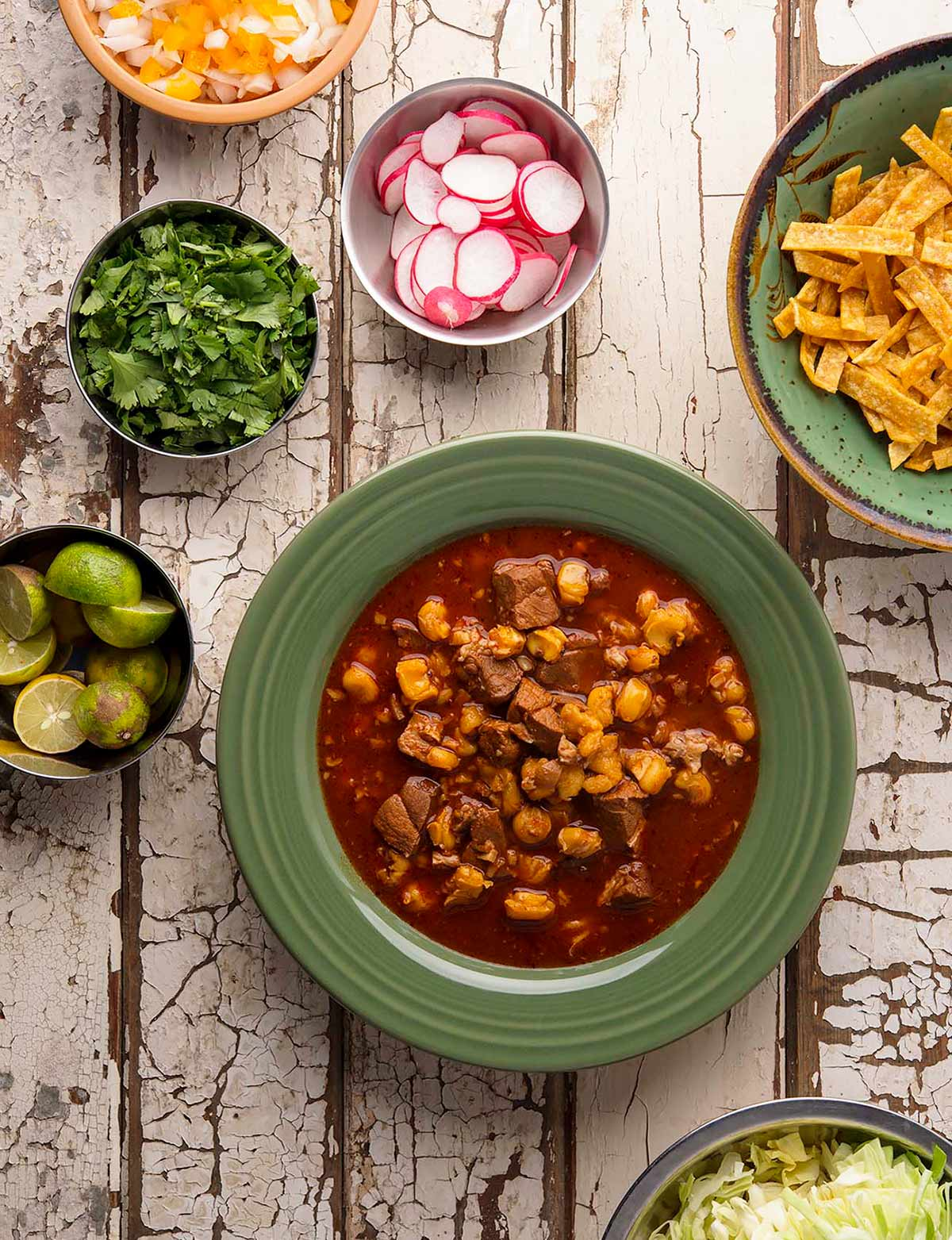 pozole rojo in a bowl with all the fixins