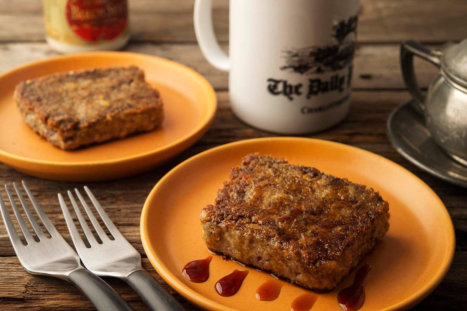 Two plates of scrapple with a cup of coffee.