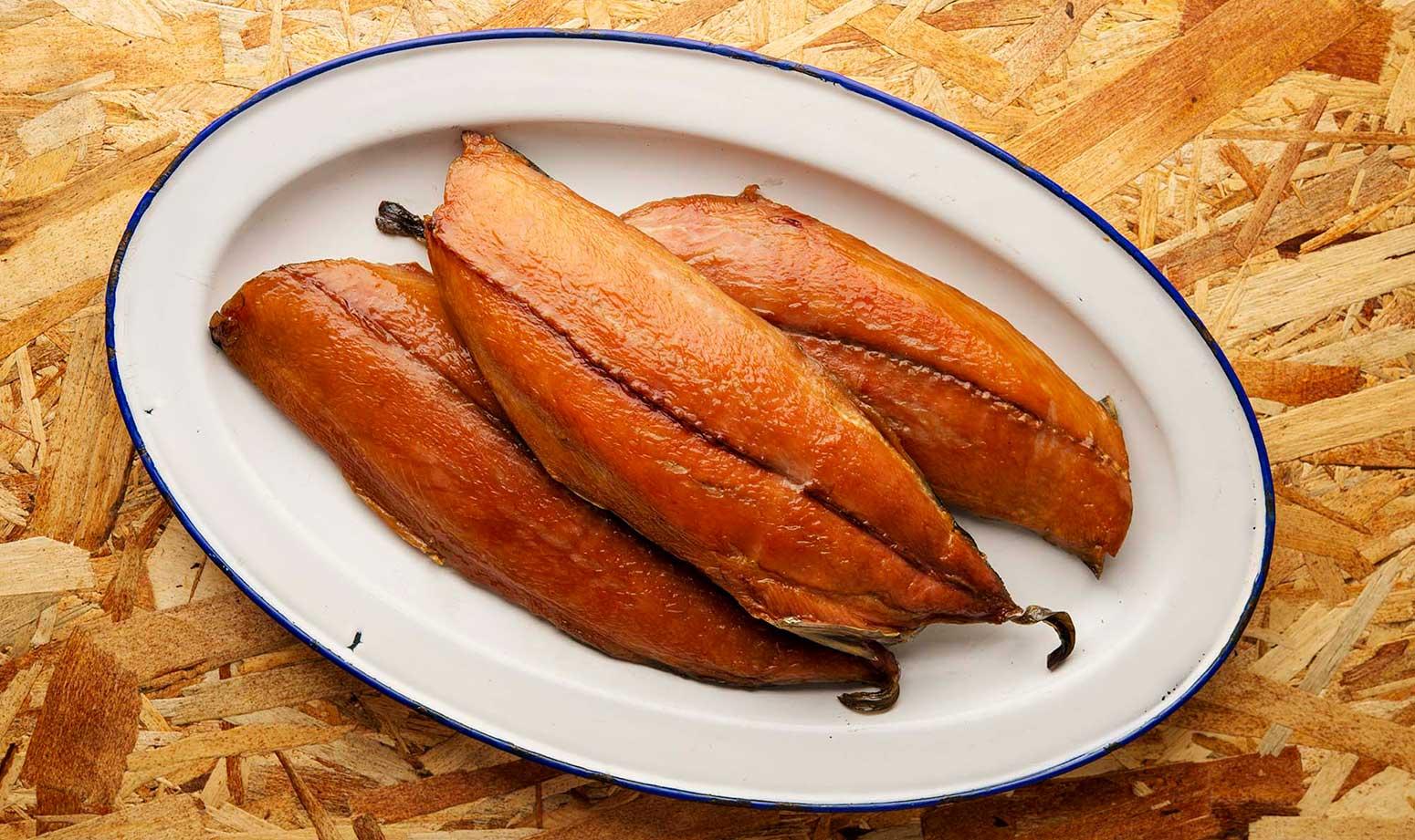 Three fillets of smoked bonito fish on a platter.
