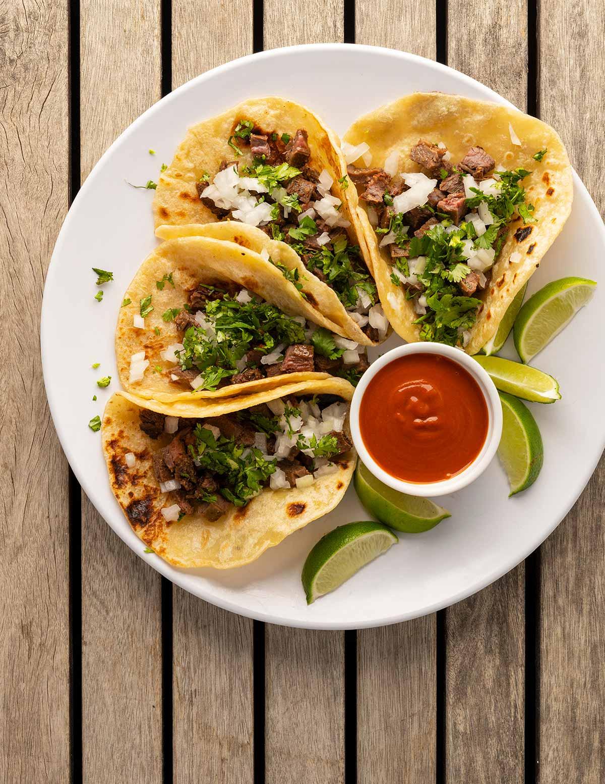 A plate of arrachera tacos with salsa