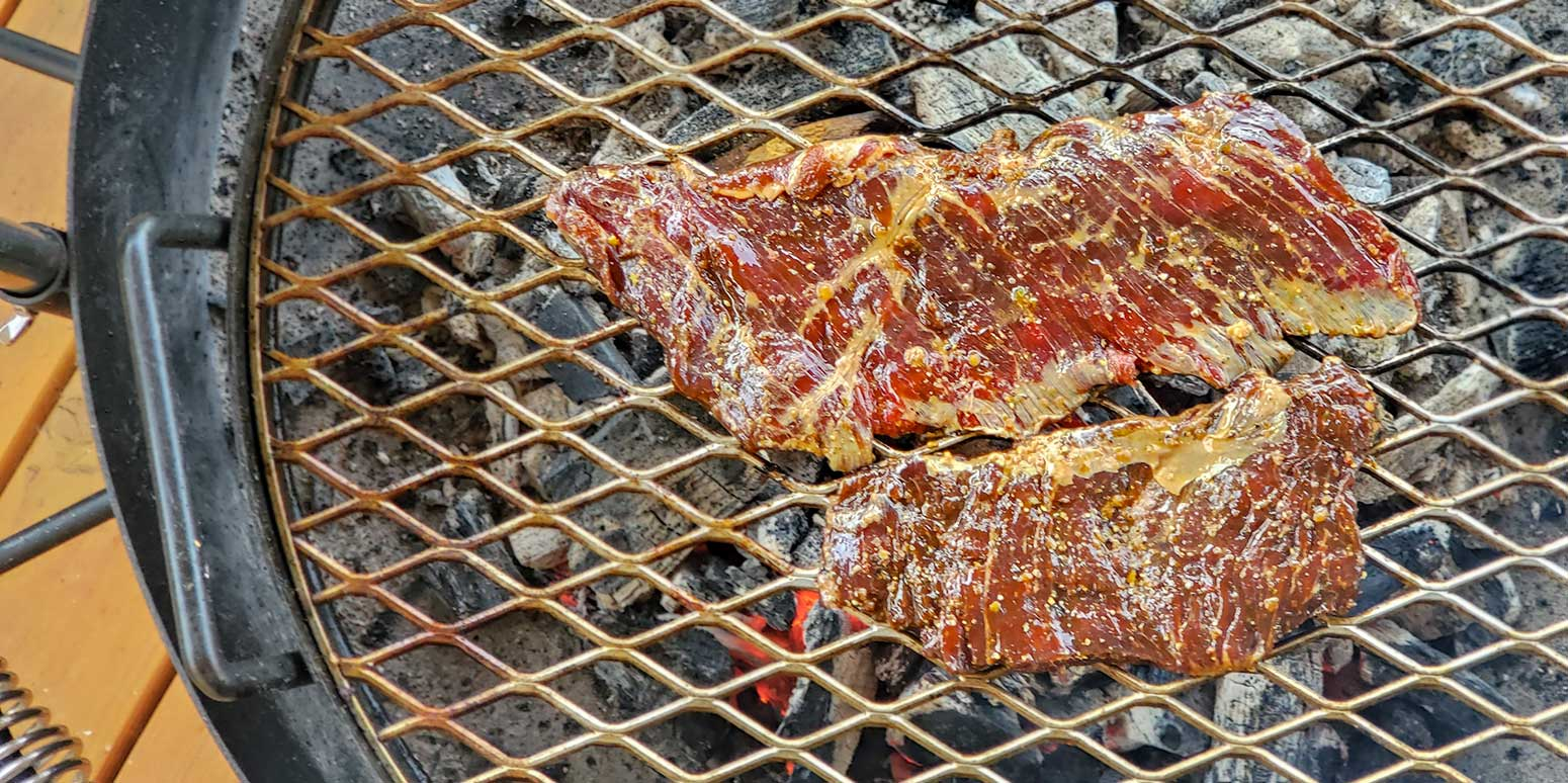 Grilled skirt steak just hitting the hot grill grates