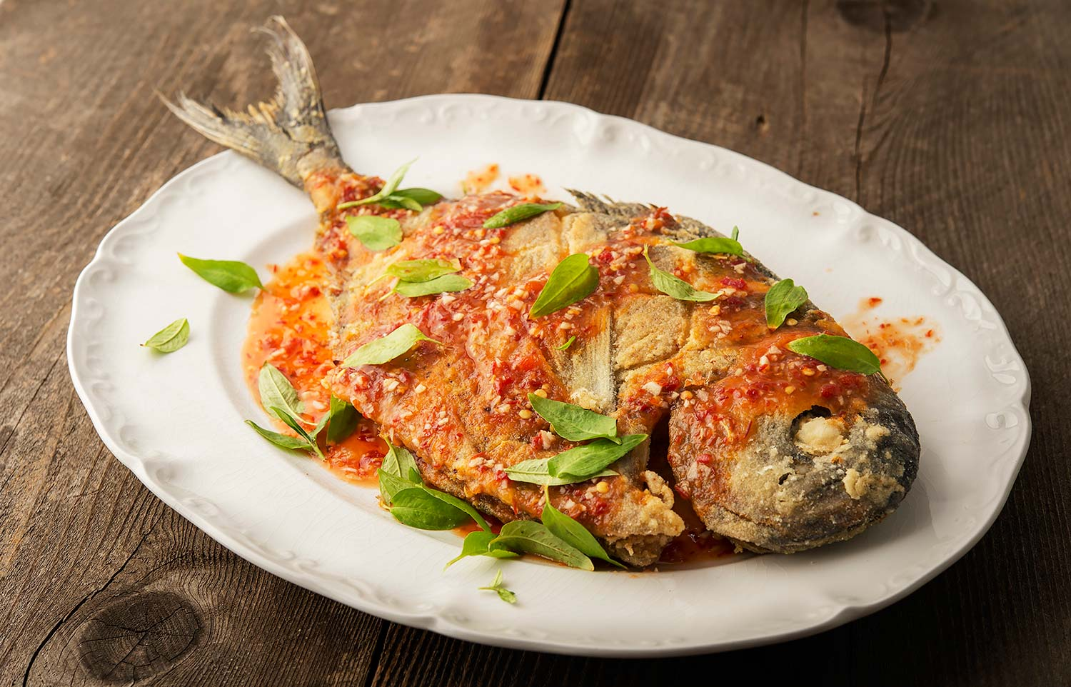 Thai fried pomfret fish with chile sauce on a platter.