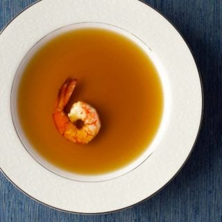 A bowl of shrimp stock with one shrimp in it