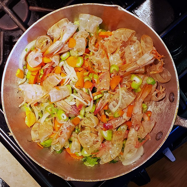 Ingredients for shrimp stock in a pan