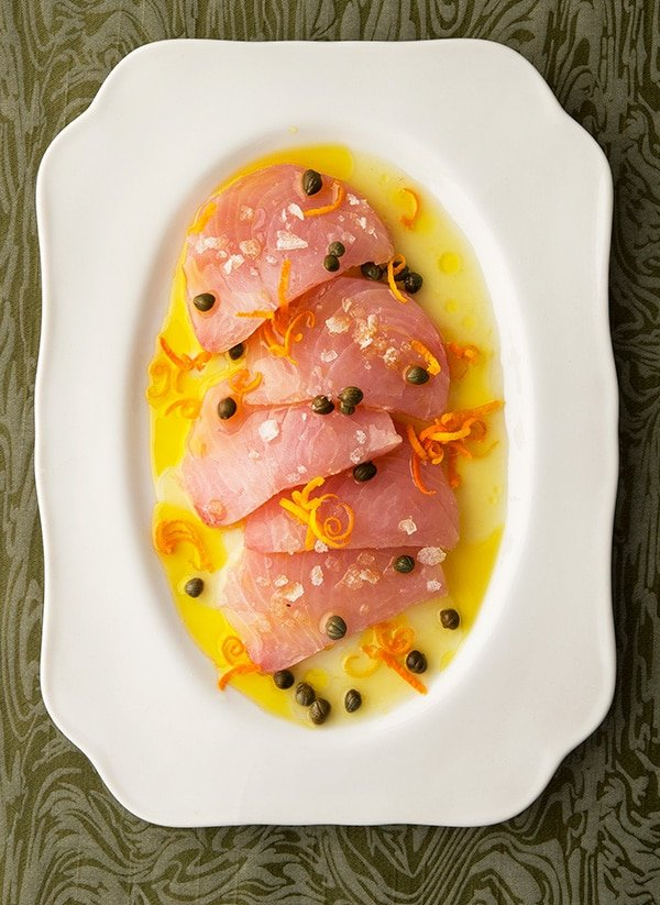 Slices of tuna crudo on a platter