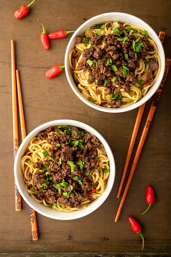 An overhead view of two bowls of dan dan noodles