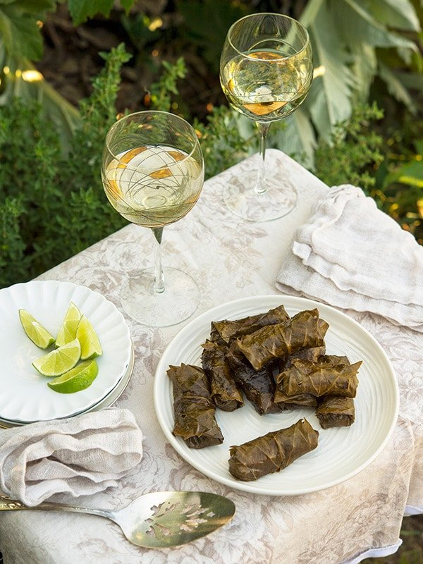 Grape leaf tamales on a plate with some white wine and limes.