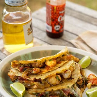 Tacos gobernador with a beer and hot sauce