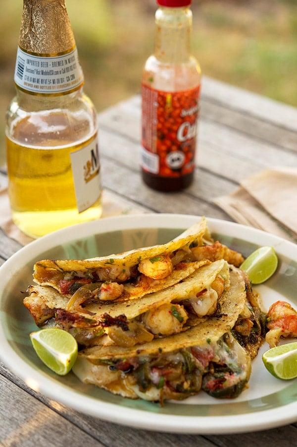 Tacos gobernador with a beer and hot sauce