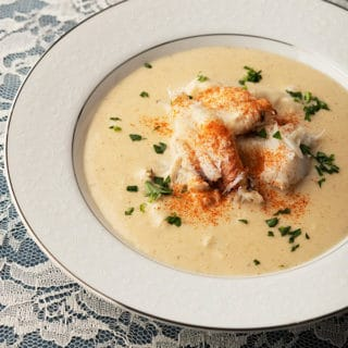Recipe for cram of crab soup in a bowl, garnished with paprika and parsley
