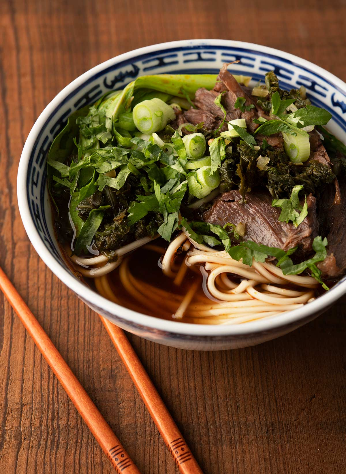 Close up of a bowl of Taiwanese beef noodle soup showing the herbs and bok choy.