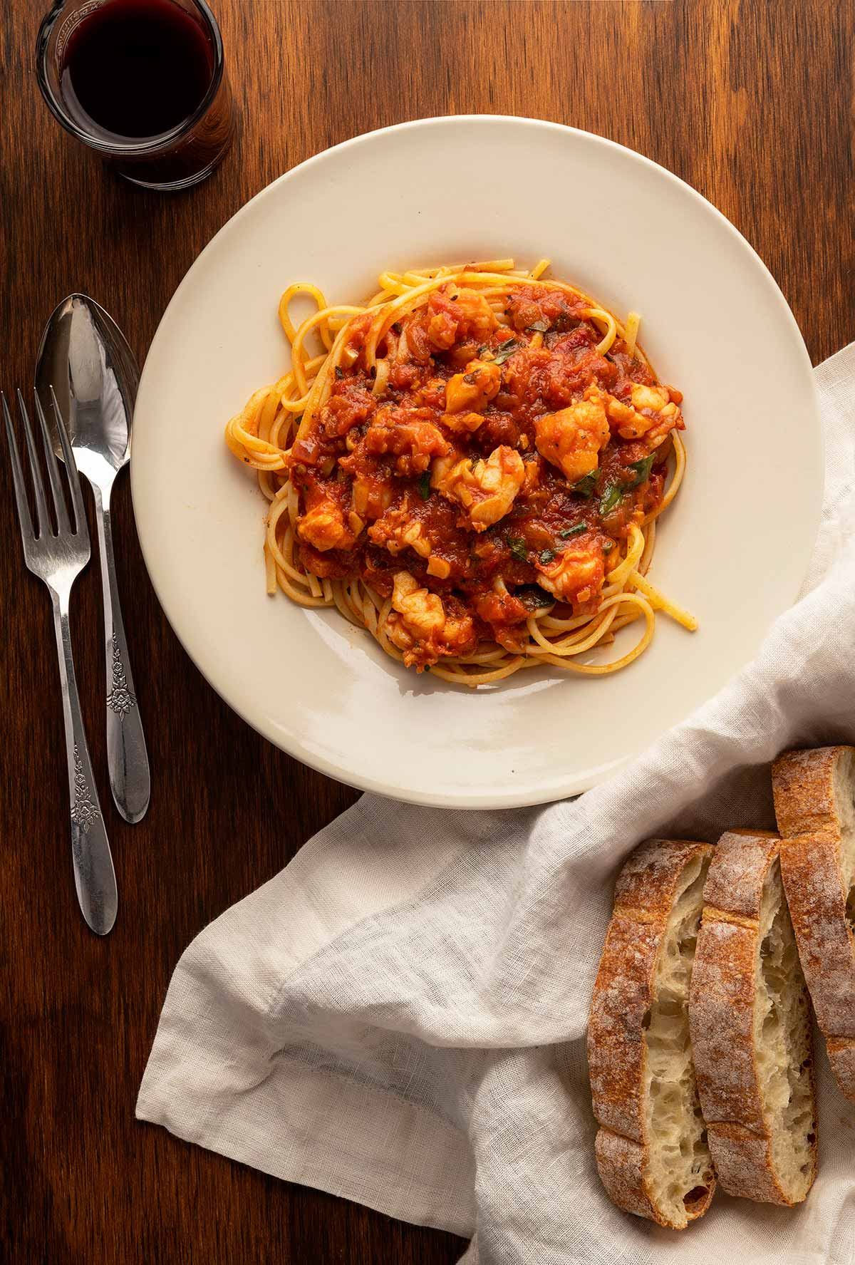 lobster fra diavolo with pasta and bread on a plate.