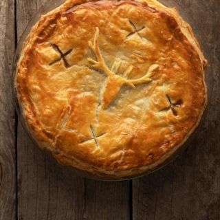 A venison and kidney pie uncut, on the table.