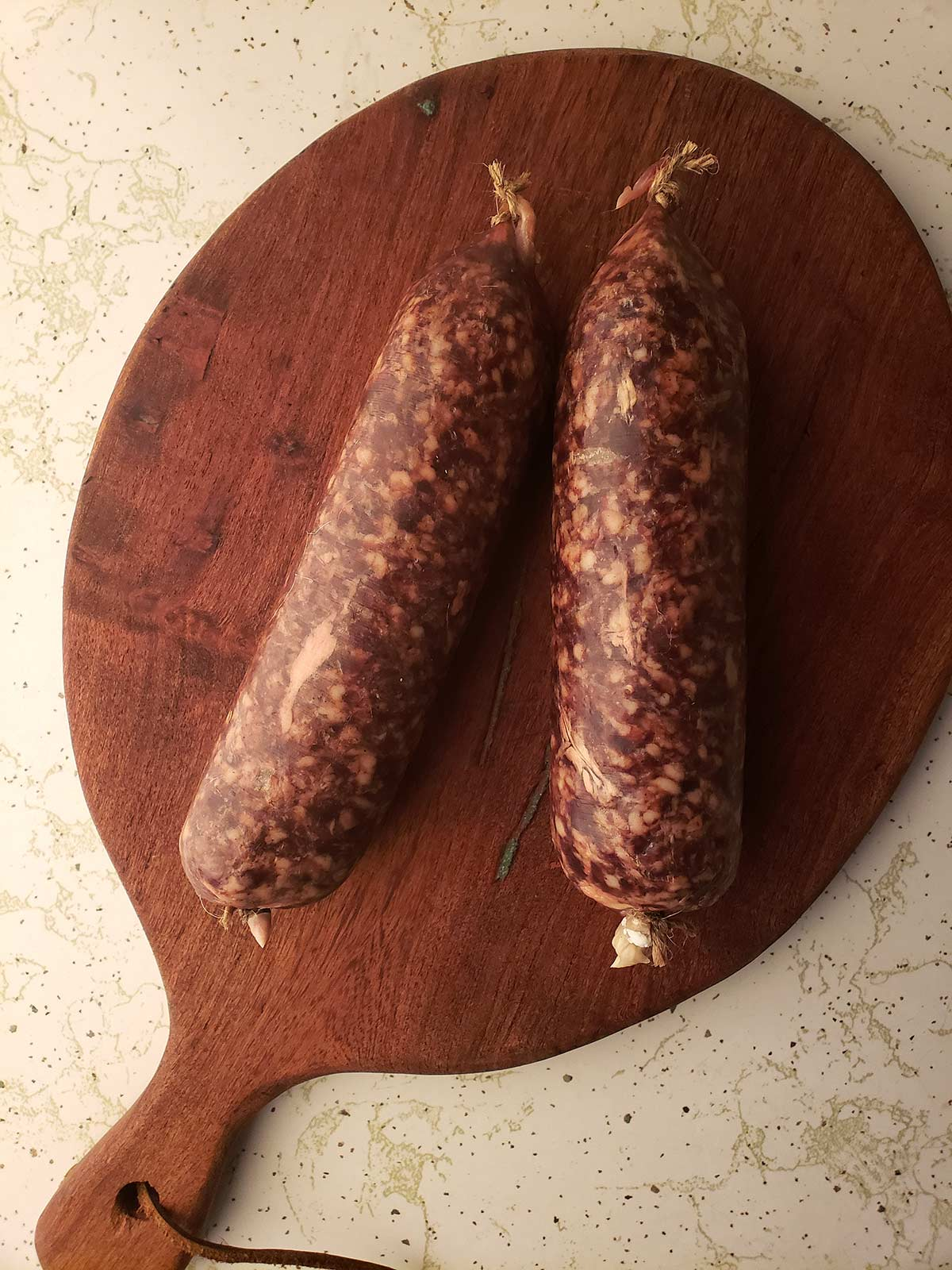 Uncooked cotechino on a cutting board