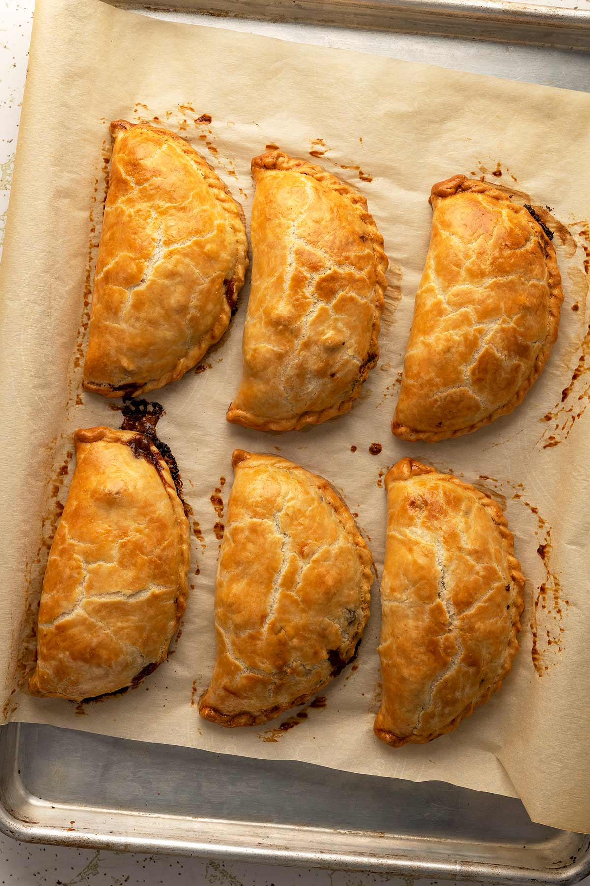 Venison pasties, cooling on a baking sheet