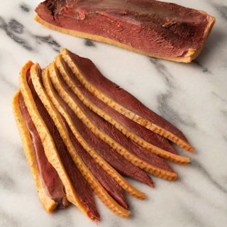 Slice of duck bacon on a marble board
