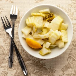 Pickled fennel in a bowl with appetizer forks