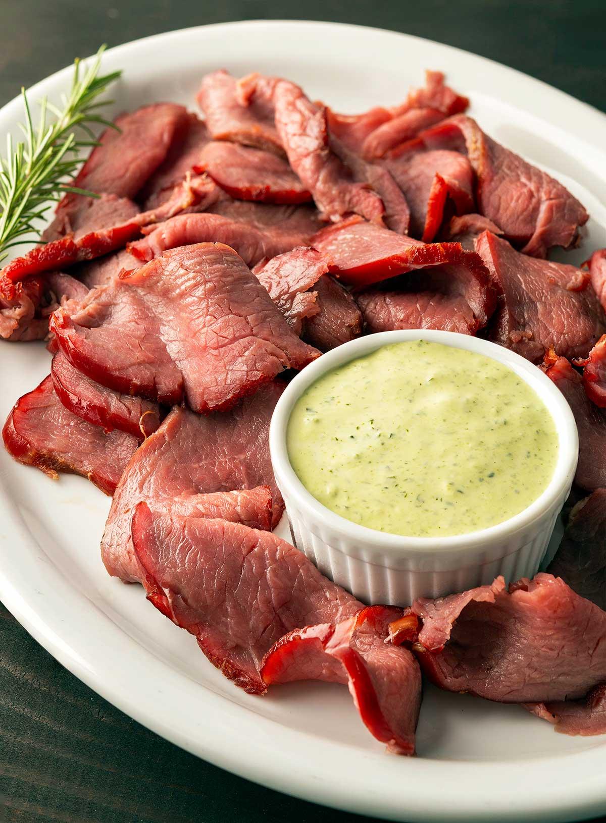 Closeup of sliced, smoked venison backstrap on a platter