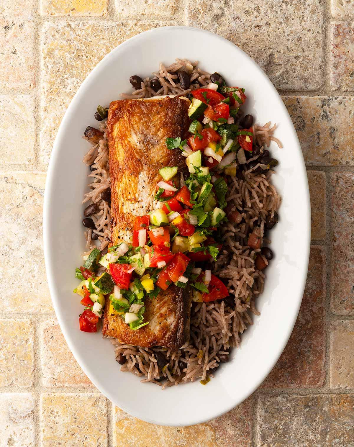A plate of pan seared mahi mahi with rice and salsa