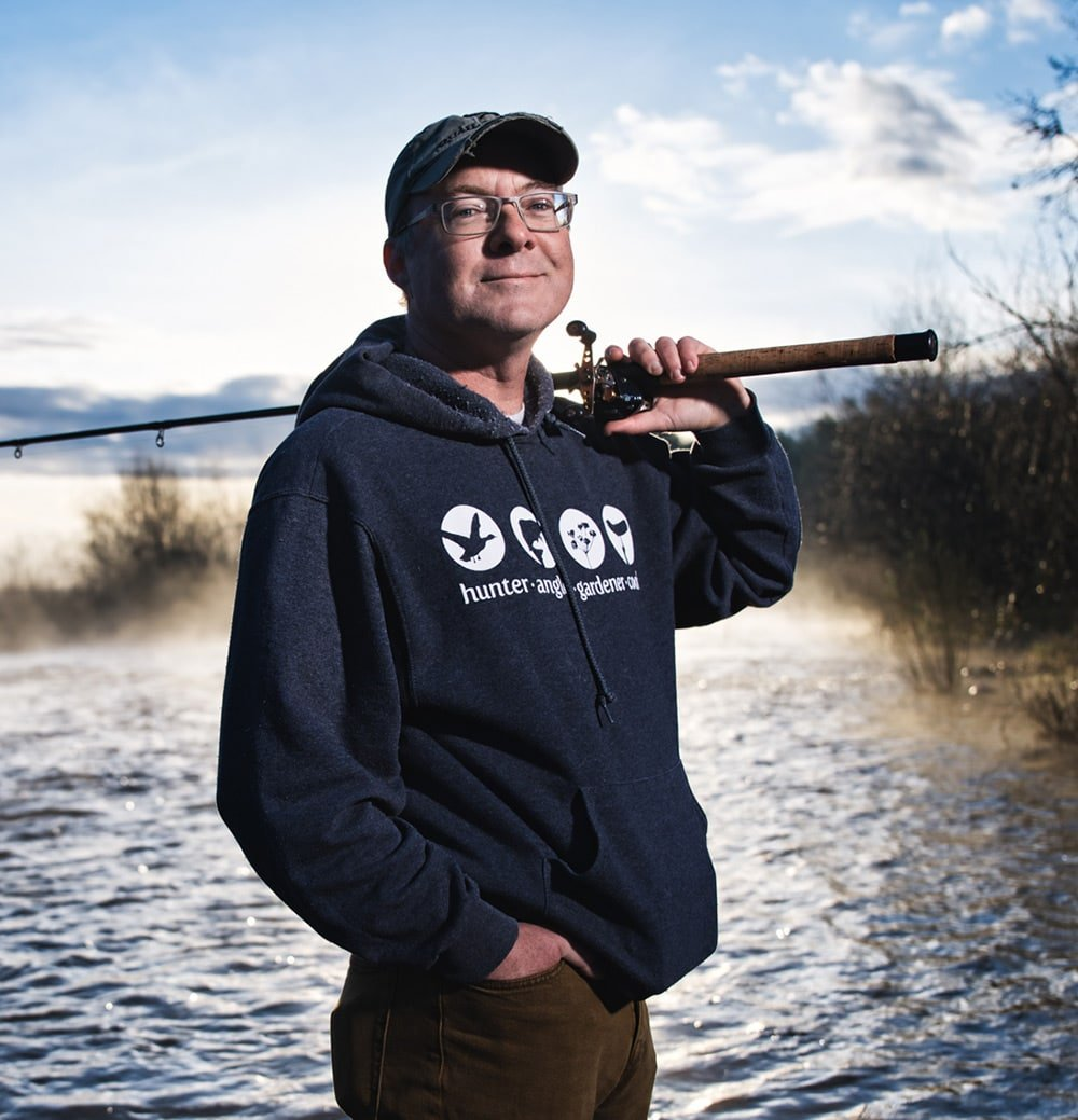 Hank Shaw holding a rod and reel in the American River