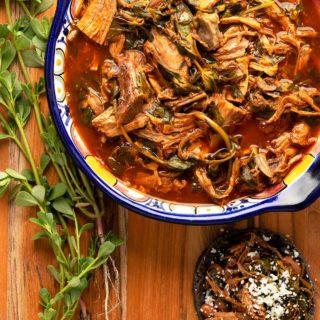 A bowl of puerco con verdolagas, pork with purslane